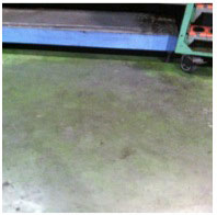 Work area stained with cutting oil, lube oil and grease prior to cleaning